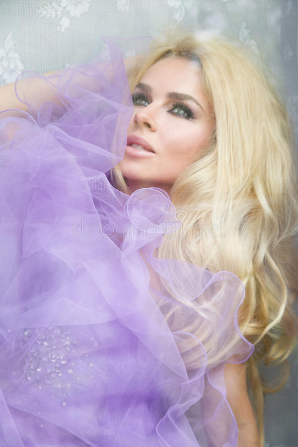 Free Portrait Of A Beautiful Blond Woman With Long, Curly Hair That Sits Behind The Glass Window, Wrapped In A Purple Tulle Stock Photos - 55954333