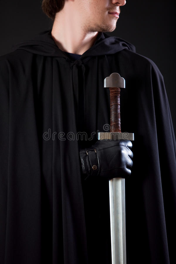 Free Portrait Of A Courageous Warrior Wanderer In A Black Cloak And Sword In Hand. Royalty Free Stock Image - 83869736