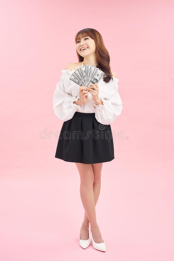Free Portrait Of A Happy Satisfied Girl Holding Bunch Of Money Banknotes And Looking At Camera Isolated Over Pink Background Stock Photography - 176670602