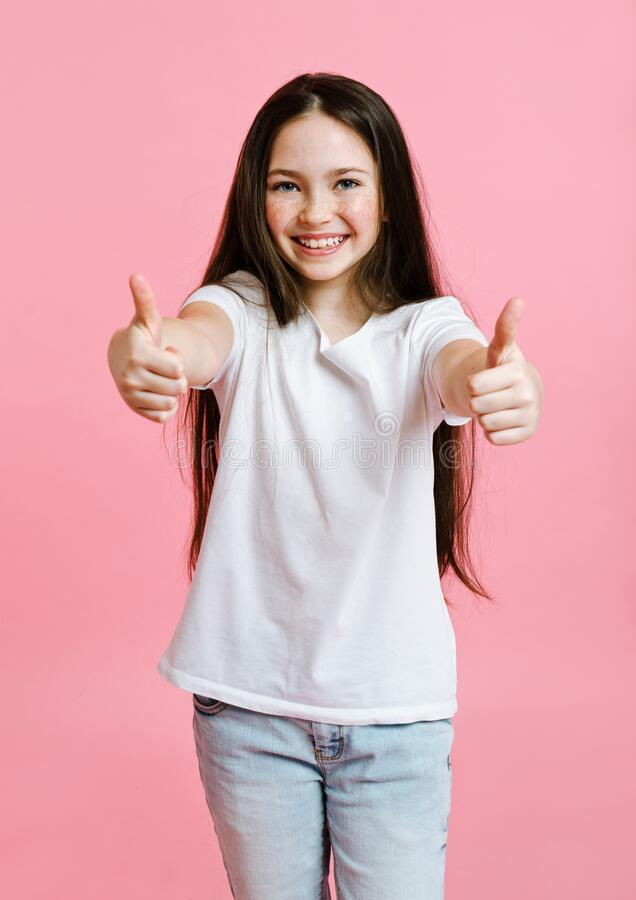 Free Portrait Of Adorable Smiling Little Girl Child In The White T-shirt With Two Fingers Up Isolated On A Pink Stock Images - 180106854