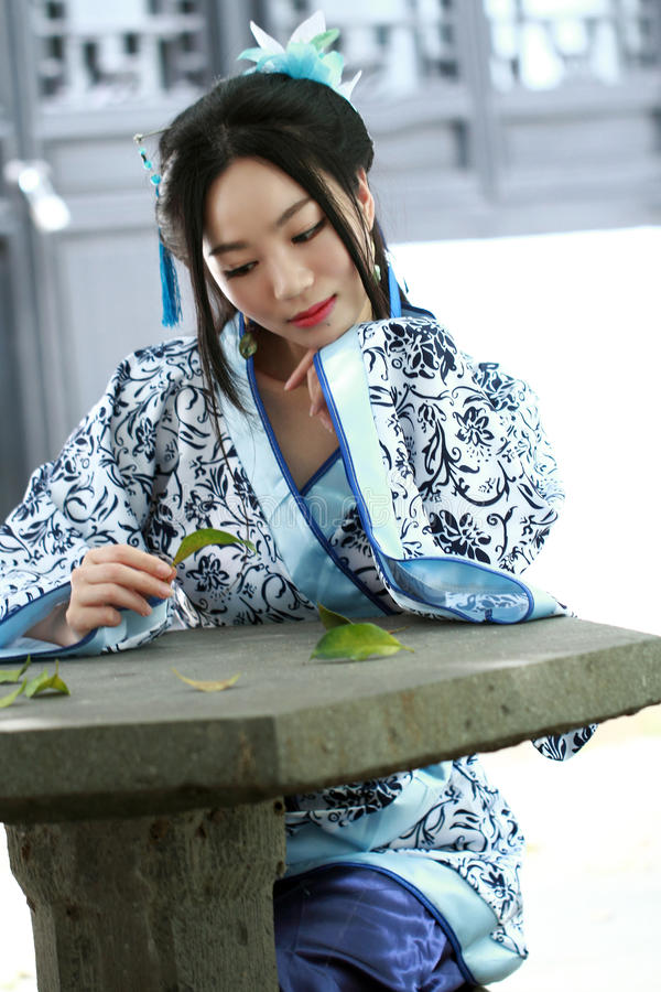 Free Portrait Of Asian Chinese Girl In Traditional Dress, Wear Blue And White Porcelain Style Hanfu, Sit On A Stone Chair Stock Photo - 93534270