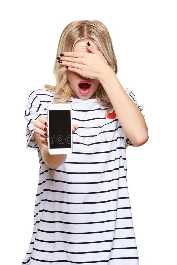 Free Portrait Of Shocked Pretty Blond Young Woman Covering Her Eyes With Hand Showing Mobile Phone Blank Screen Isolated Over White. Stock Photo - 160358290