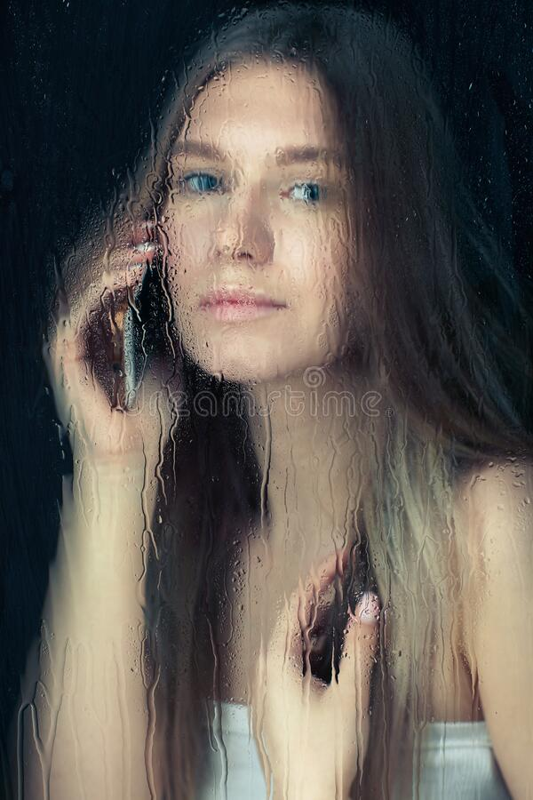 Free Portrait Of Young Blonde Woman With Phone Hands Behind The Window Glass With Raindrops Royalty Free Stock Photos - 214689958