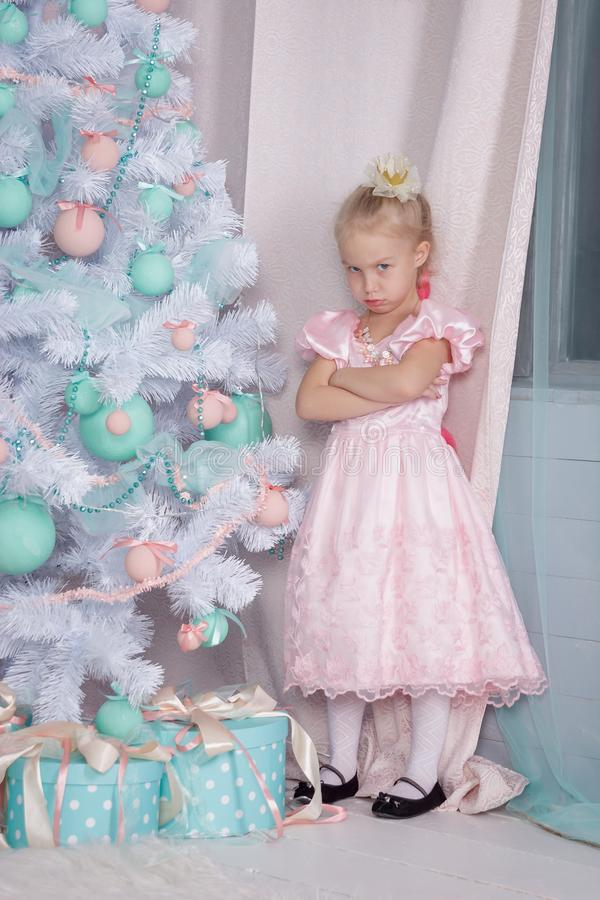 Portrait of an offended and frustrated European little blonde Princess girl royalty free stock image