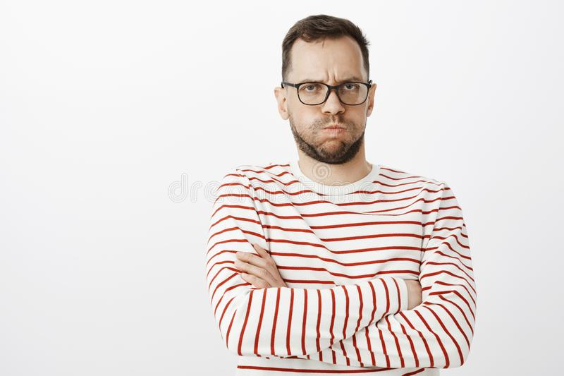 Portrait of offended gloomy gay boyfriend, pouting and frowning, crossing hands on chest while being angry on lover. Waiting for cuddle or sorry, standing royalty free stock photography