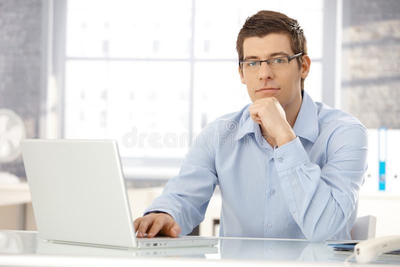 Portrait of office worker with laptop. Portrait of office worker man sitting at office desk using laptop computer, looking at camera royalty free stock image