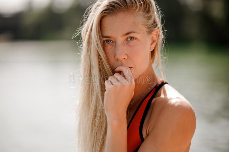 Portrait og young blonde woman dressed in red swimsuit. Standing on the background on water with hand near face stock photos