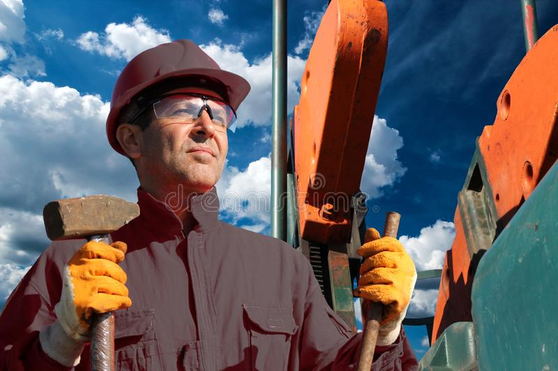Portrait of Oil Worker at Oil Well. Oilfield Jobs Concept. Oil worker holding sledgehammer in front of pump jack oil well against cloudy blue sky in background royalty free stock photography