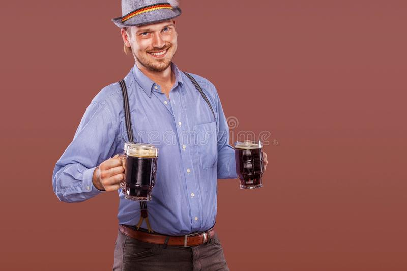 Portrait of Oktoberfest man in hat, wearing a traditional Bavarian clothes, serving big beer mugs. royalty free stock image