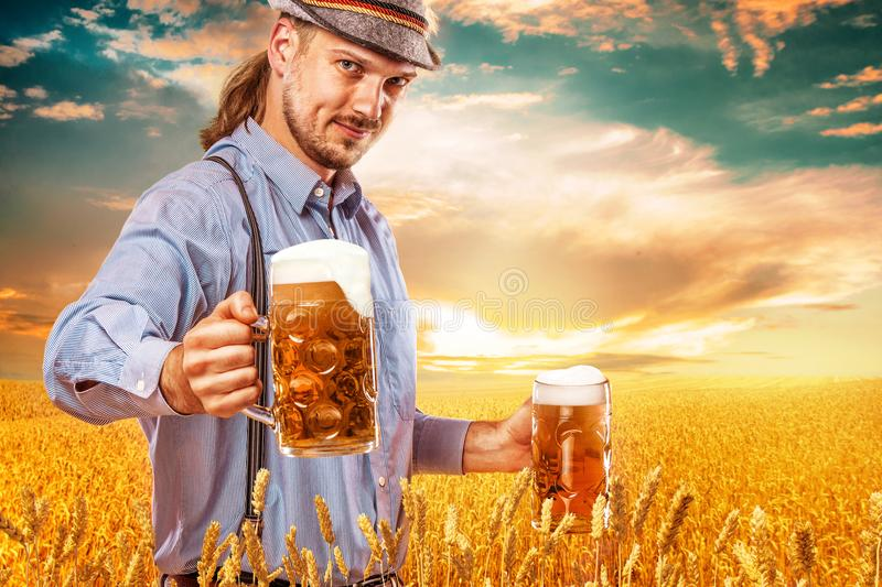 Portrait of Oktoberfest man, wearing a traditional Bavarian clothes, serving big beer mugs. royalty free stock photography