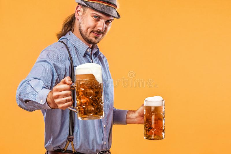 Portrait of Oktoberfest man, wearing a traditional Bavarian clothes, serving big beer mugs. stock image