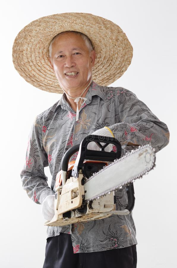 Asian old man holding chainsaw stock photography