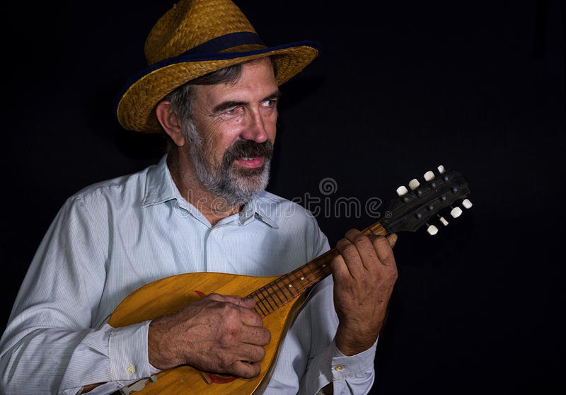 Portrait of an old country man with mandolin. Portrait (low key) of an old country man with mandolin royalty free stock photos