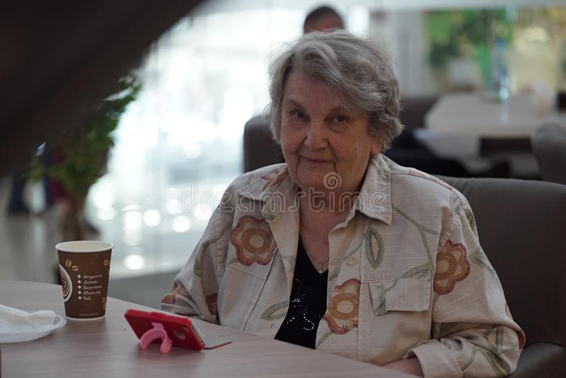Portrait of old smiling woman in the cafe. Portrait of old elderly smiling woman dressed in grey cotton shirt sitting in cafe. Communication over smart phone stock images