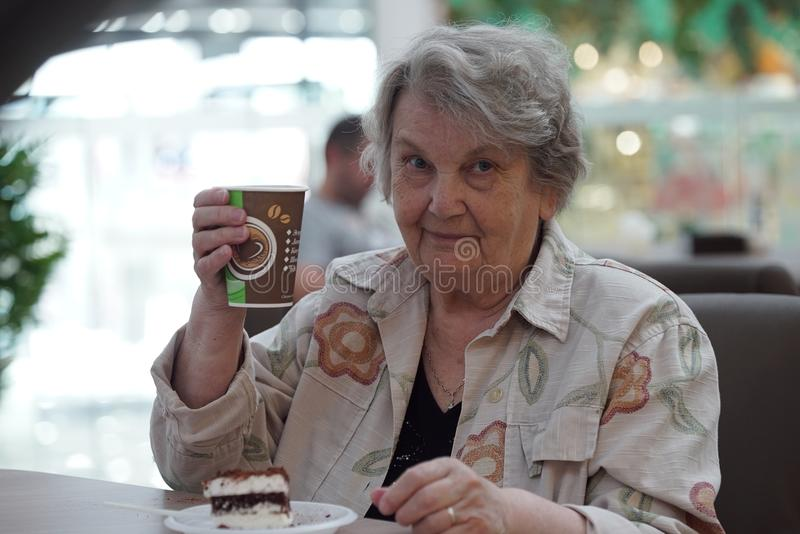 Portrait of old smiling woman in the cafe. Portrait of old elderly smiling woman dressed in grey cotton shirt sitting in cafe holding cup of coffee. Wonderful royalty free stock photo