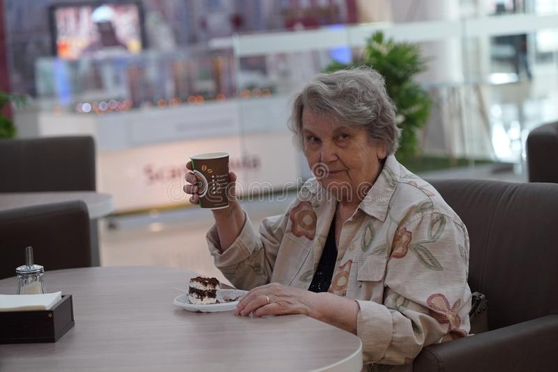 Portrait of old smiling woman in the cafe. Portrait of old elderly smiling woman dressed in grey cotton shirt sitting in cafe holding cup of coffee. Wonderful stock images