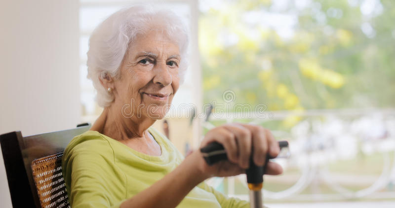 Portrait Old Lady Sitting On Rocking Chair Holding Stick royalty free stock images