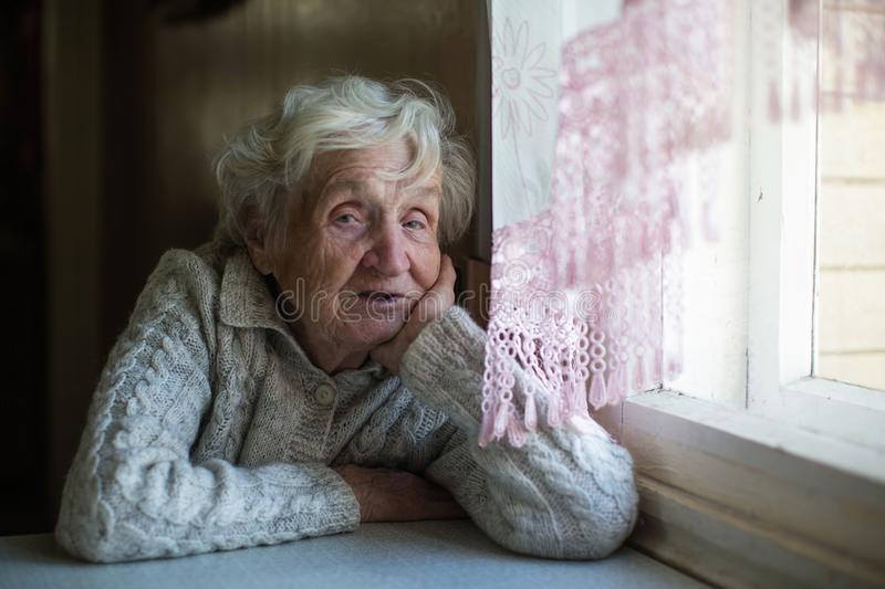Portrait of old lady sitting at the table. stock image
