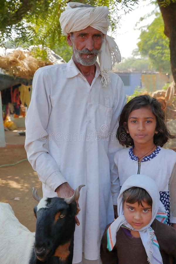 BUNDI, RAJASTHAN, INDIA - DECEMBER 09, 2017: Portrait of an old man dressed in white posing with two children and a goat in a vill stock photography