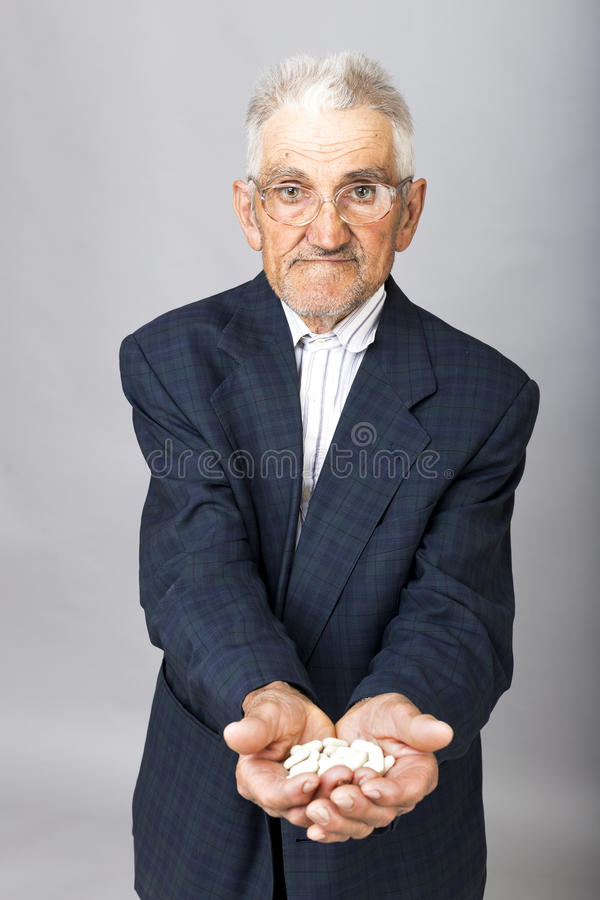 Portrait of an old man with glasses holding a lot of pills in hi stock image