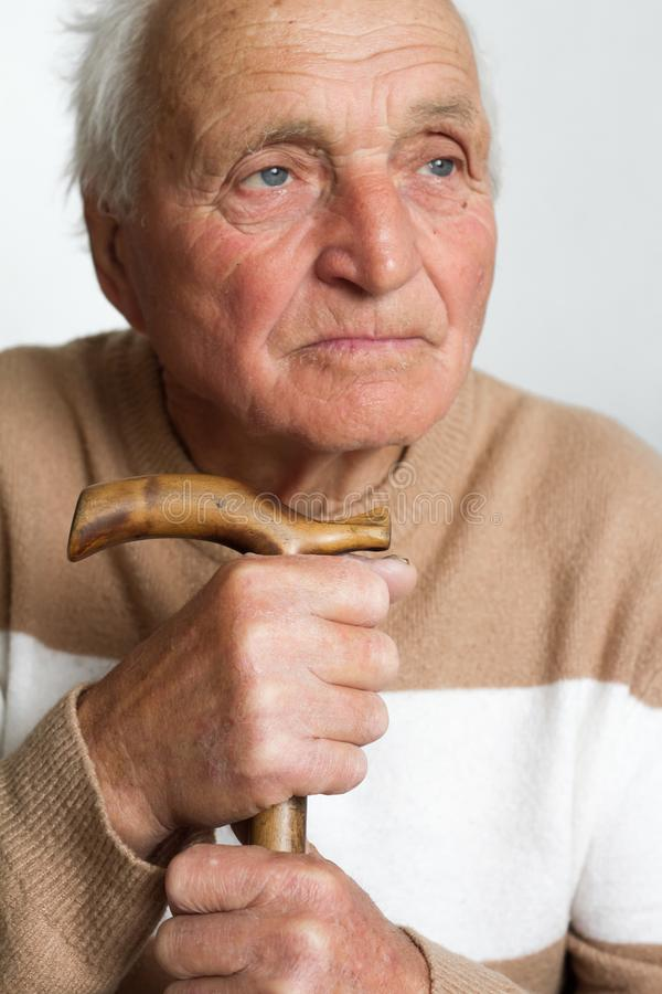 Portrait of an old sad man who put his head on the handle of a wooden cane. The concept of loneliness at home royalty free stock images