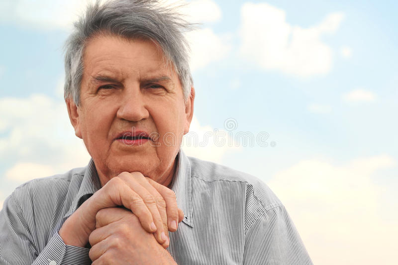 Portrait of old serious senior in striped shirt stock image
