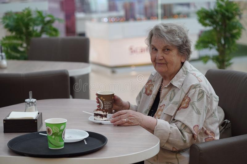 Portrait of old smiling woman in the cafe. Portrait of old elderly smiling woman dressed in grey cotton shirt sitting in cafe holding cup of coffee. Wonderful stock photo