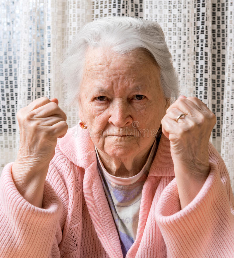 Portrait of old woman in angry gesture stock images