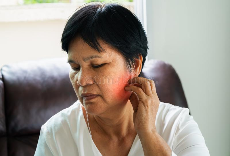 Portrait of old woman have toothache at home stock image