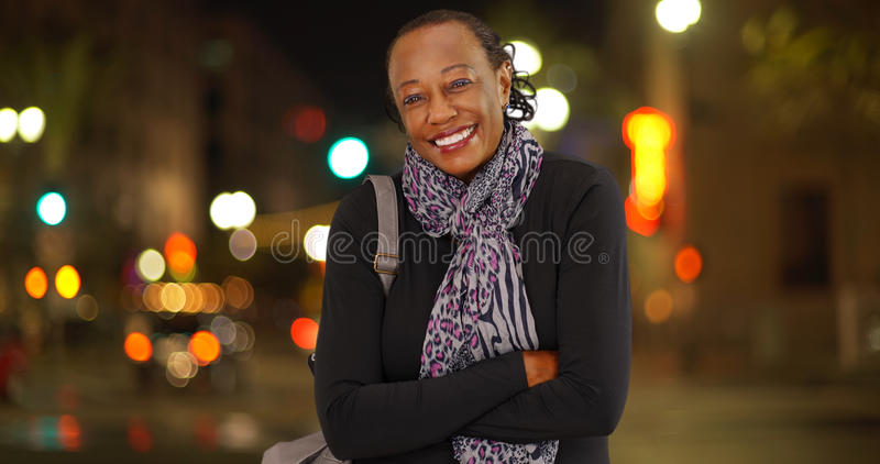 A portrait of an older African American woman laughing in the cold weather on a busy street corner royalty free stock image