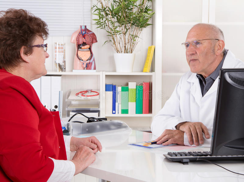 Portrait: older doctor with experience talking with senior woman. Portrait: older doctor with experience talking with senior women sitting at desk stock photo