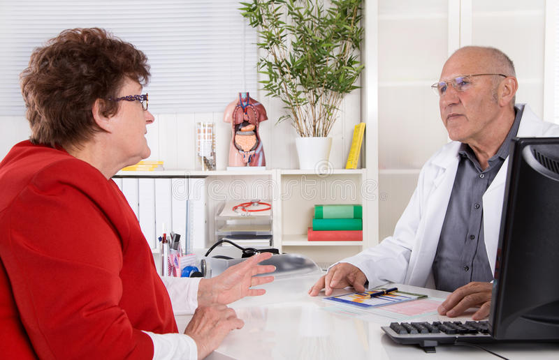 Portrait: older doctor with experience talking with senior woman. Portrait: older doctor with experience talking with senior women sitting at desk royalty free stock images