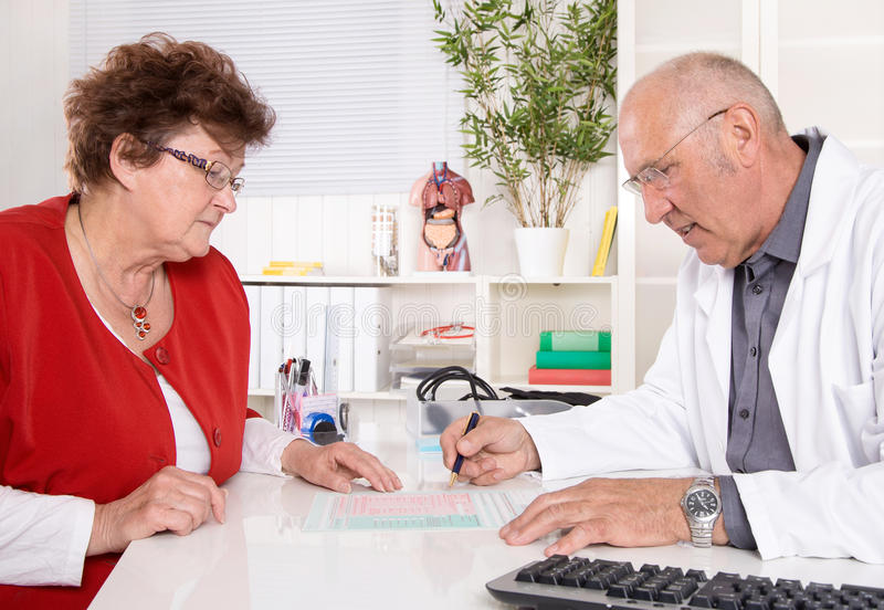 Portrait: older doctor with experience talking with senior woman. Portrait: older doctor with experience talking with senior women sitting on the table royalty free stock images
