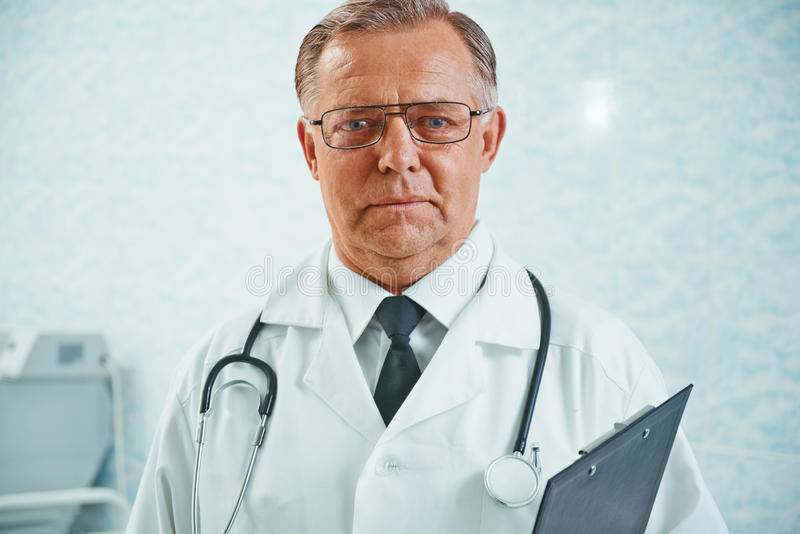 Portrait of older doctor. Portrait of older man doctor with documents in hospital royalty free stock photo