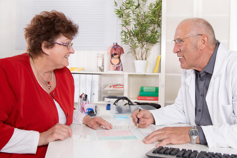 Portrait of an older doctor talking with a female patient. Portrait of an older doctor talking with a female patient sitting at desk royalty free stock photo