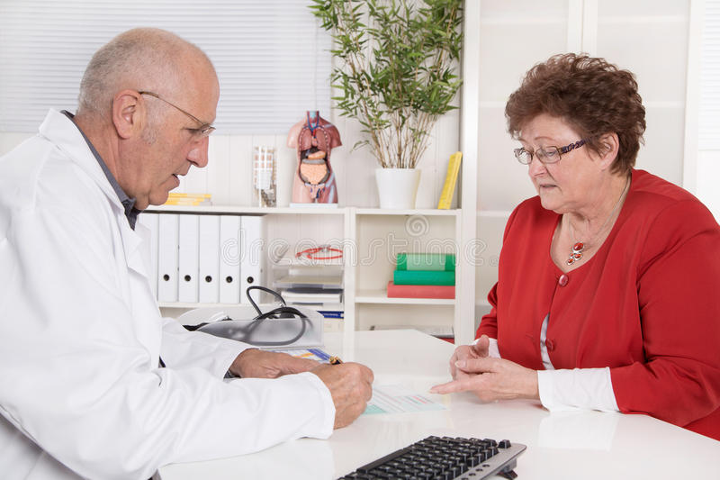 Portrait of an older doctor talking with his female patient. Portrait of an older doctor talking with his female patient sitting at desk stock photography