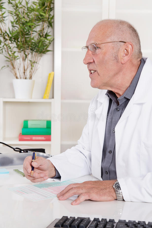 Portrait of an older male doctor sitting at desk. Portrait of an older senior doctor sitting at desk stock image