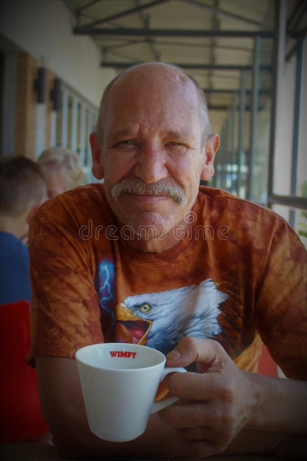 Portrait of an older man drinking coffee, Newmarket Mall, Alberton royalty free stock photo