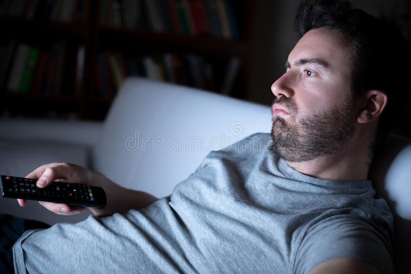 Lazy man watching television at night alone. Portrait of one caucasian man watching tv royalty free stock photography