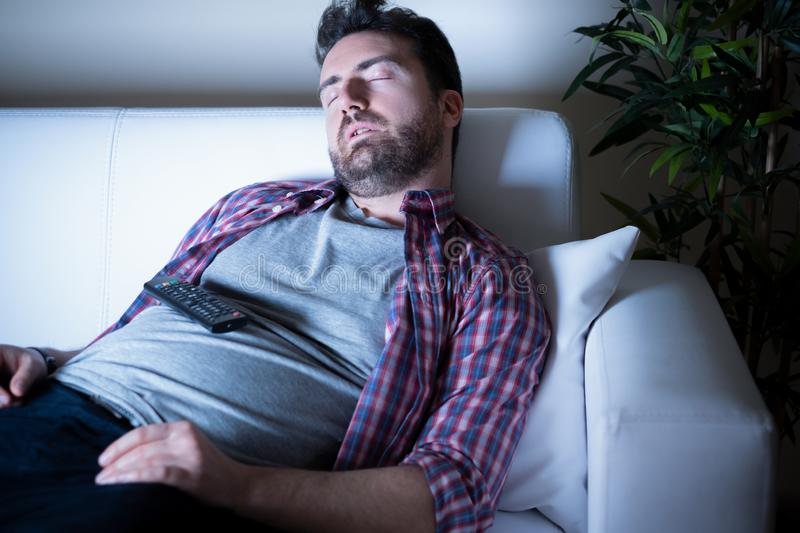 Portrait of one caucasian man watching tv. Lazy man watching television at night alone stock photography