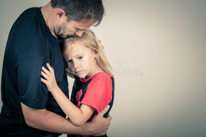 Portrait of one sad daughter hugging her father. Near the wall royalty free stock photo