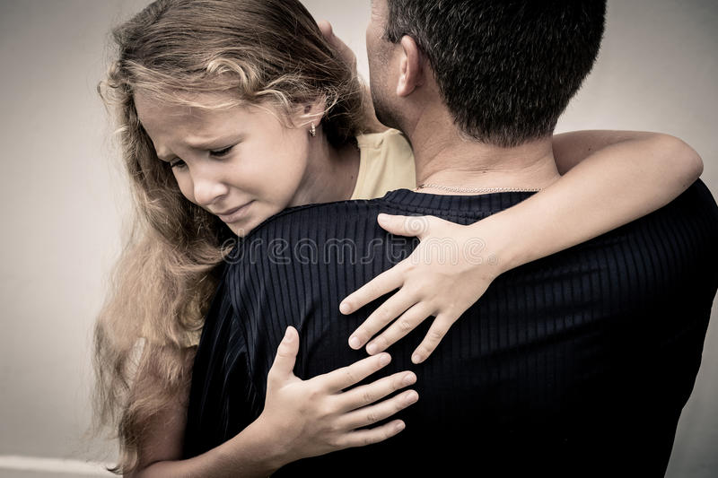 Portrait of one sad daughter hugging his father. At the day time royalty free stock image