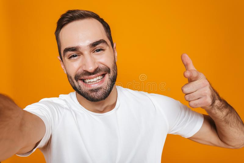 Portrait of optimistic man 30s in t-shirt laughing while taking selfie photo, isolated over yellow background stock image