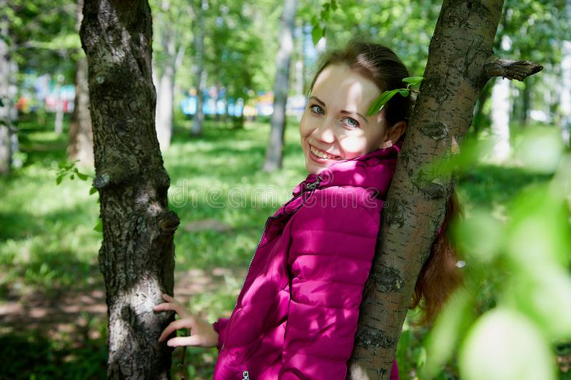Portrait of a ordinary cute girl in the green park with blossoming apple tree with white flower in a springtime stock photos