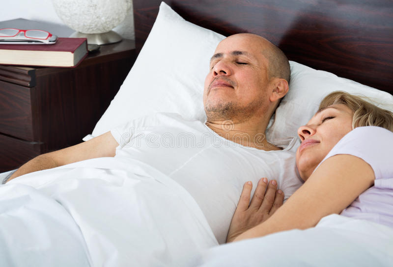 Portrait of ordinary mature couple napping in bed stock photos