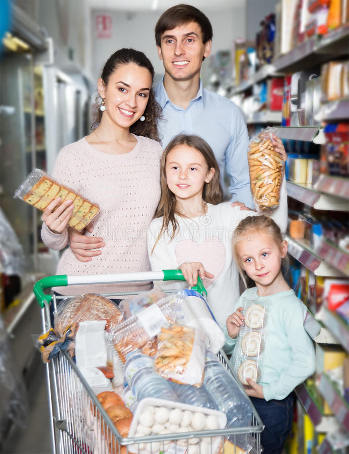 Portrait of ordinary satisfied family in local supermarket. Portrait of ordinary satisfied family with two children in local supermarket stock photos