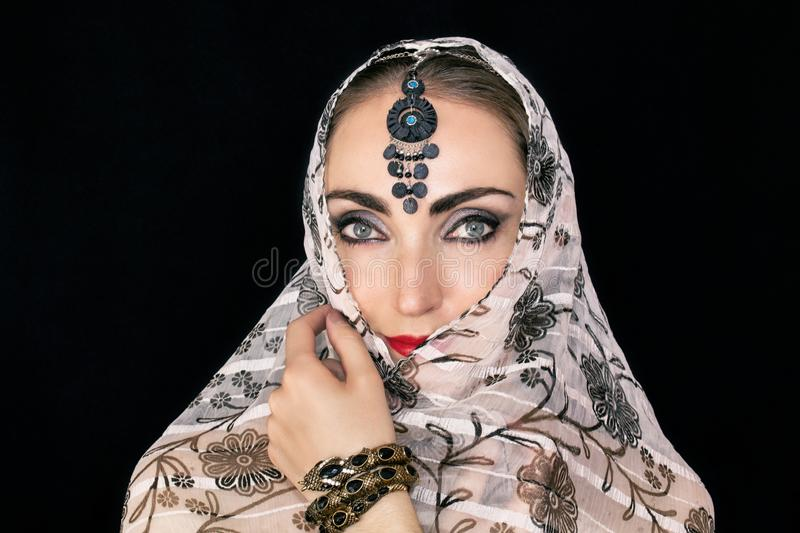 Portrait of an oriental young woman in a scarf with an ornament and jewels on a black background stock image