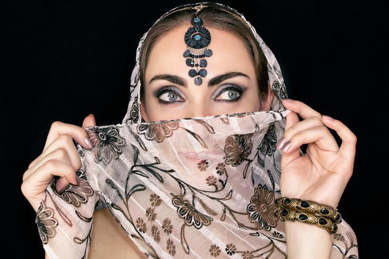Portrait of an oriental young woman in a scarf with an ornament and jewels on a black background stock photography
