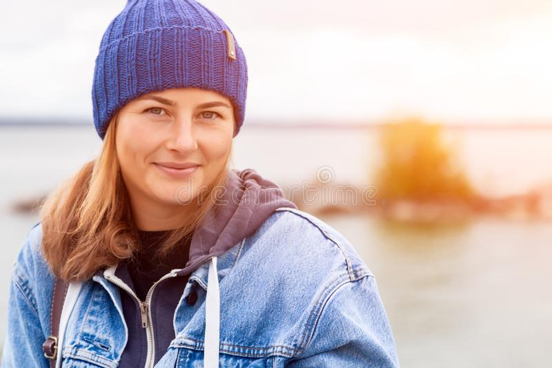 Portrait of outdoor atmospheric lifestyle photo. Of young beautiful darkhaired woman in knitting hat, in a denim jacket and black trousers against the stock image