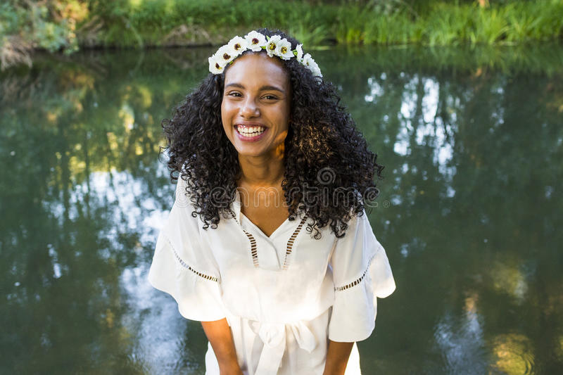 portrait outdoors of a beautiful young afro american woman smiling at sunset. Green background. Lifestyle stock image